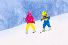 Deux enfants skiant en montagnes neigeuses Image stock