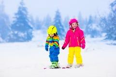 Deux enfants skiant en montagnes neigeuses Photographie stock libre de droits
