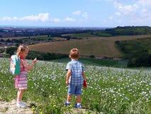 Deux enfants sur les collines du Sussex, un examinant sa fleur et l'autre la vue images stock