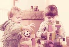 Deux enfants tranquilles jouant avec les blocs en bois Image libre de droits