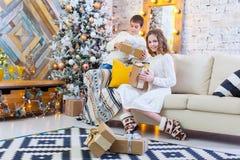 Deux enfants un garçon et une fille à un arbre de Noël sur un sofa avec des cadeaux En couleurs les couleurs claires Image libre de droits