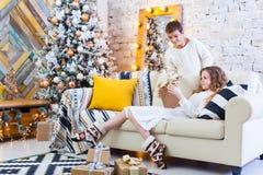 Deux enfants un garçon et une fille à un arbre de Noël sur un sofa avec des cadeaux En couleurs les couleurs claires donnez les p Images libres de droits