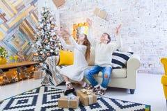 Deux enfants un garçon et une fille à un arbre de Noël sur un sofa avec des cadeaux En couleurs les couleurs claires jetez les ca Photographie stock