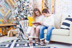 Deux enfants un garçon et une fille à un arbre de Noël sur un sofa avec des cadeaux En couleurs les couleurs claires Lisez le liv Images stock
