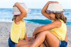 Deux enfants utilisant des chapeaux sur la plage Photo libre de droits