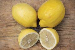 Deux entiers et deux moitiés des citrons au centre de la planche à découper en bois Photographie stock libre de droits