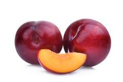 Deux entiers et tranche de prunes de cerise rouges d'isolement sur le blanc Photographie stock libre de droits