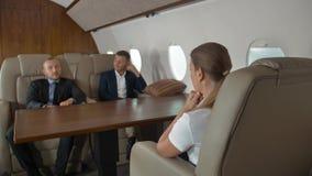 Deux entrepreneurs masculins sûrs et jet femelle réussi de première classe d'intérieur de femme d'affaires banque de vidéos