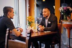 Deux entretiens d'hommes et à l'aide d'un ordinateur portable dans un restaurant Photographie stock libre de droits