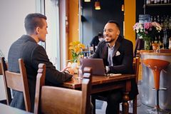 Deux entretiens d'hommes et à l'aide d'un ordinateur portable dans un restaurant Photo stock