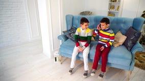 Deux entretiens de frère de garçons au téléphone portable avec la grand-mère consécutivement, se reposant sur le sofa bleu dans l clips vidéos