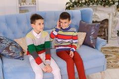 Deux entretiens de frère de garçons au téléphone portable avec la grand-mère consécutivement, s photographie stock