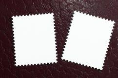 Deux estampilles en blanc sur un fond en cuir rouge Photos stock