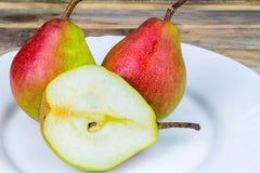 Deux et demi poires dans le plat blanc, table en bois rustique Images stock