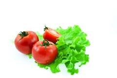 Deux et tomates à moitié rouges sur des lames de laitue Image libre de droits