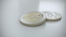 Deux euro pièces de monnaie sur une surface réfléchie blanche Photos libres de droits