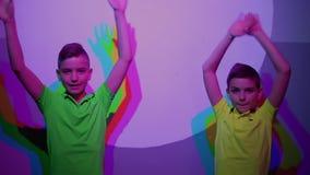 Deux expositions mignonnes de garçons manie maladroitement, les ombres colorées sur le mur