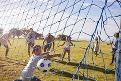 Deux familles jouant le football en parc, marquant un but Photos stock