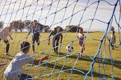 Deux familles jouant le football en parc vu par le filet de but Photos libres de droits