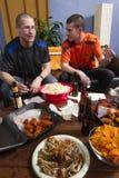 Deux fans observant le jeu de sports à la TV, verticale Images libres de droits