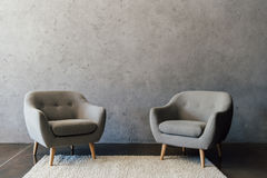 Deux fauteuils gris confortables se tenant sur le tapis blanc image stock