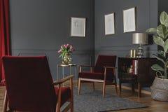 Deux fauteuils rouges se tenant dans l'intérieur gris de salon avec le MI Photo libre de droits