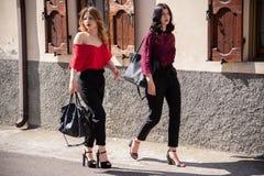 Deux femelles amicales descendent la rue photos stock
