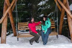 Deux femelles dans des costumes de ski et avec des lunettes de ski communiquent tandis que Photographie stock