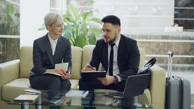 Deux femelles et collègues masculins d'affaires avec le presse-papiers et le bloc-notes parlant à l'hôtel incitent Bagage dans le banque de vidéos