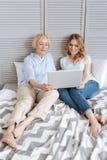 Deux femelles se sont engagées dans observer quelque chose sur l'ordinateur portable Photo stock
