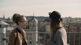 Deux femme heureuse parlant dans la perspective du panorama de ville, toits Amis marchant dedans en centre ville dans le jour ens banque de vidéos