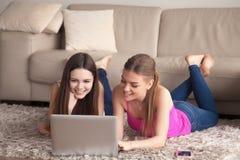 Deux femmes à l'aide de l'ordinateur portable en se trouvant sur le tapis Images stock