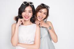 Deux femmes à la mode dans les robes intéressantes se tenant ensemble et le havi Photo stock