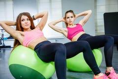 Deux femmes à un centre de fitness ensemble sur une boule de forme physique Images libres de droits