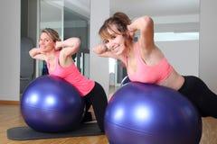 Deux femmes à un centre de fitness sur une boule de forme physique Image libre de droits