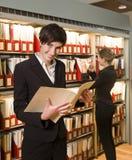 Deux femmes à une bibliothèque Photos stock