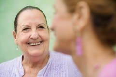 Deux femmes âgées parlant sur le banc de stationnement Image libre de droits