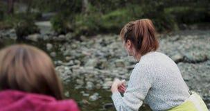 Deux femmes écrémant des pierres sur le lac banque de vidéos
