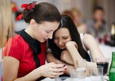 Deux femmes élégantes aux sms d'une lecture d'événement Photo stock