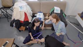 Deux femmes épuisées s'asseyent sur le plancher devant le divan avec les vêtements assortis de la garde-robe, se reposant banque de vidéos