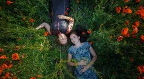 Deux femmes étendues sur le gisement de fleur de pavot Images stock