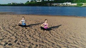 Deux femmes étirant le yoga sur la plage sablonneuse de la rivière Belle vue de ville clips vidéos