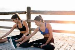 Deux femmes étirant leurs jambes comme elles s'exercent Photographie stock libre de droits