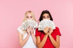 Deux femmes étonnées se cachant derrière l'argent photos stock