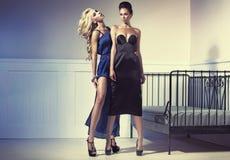 Deux femmes étonnantes utilisant les robes de soirée Image libre de droits