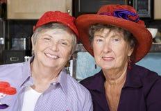 Deux femmes aînés utilisant les chapeaux rouges Photo libre de droits