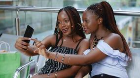 Deux femmes africaines font Selfie avec le téléphone après l'achat clips vidéos