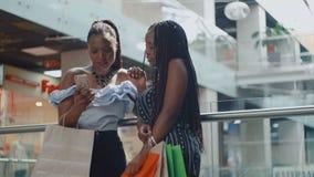 Deux femmes africaines parlant et vérifiant le smartphone après l'achat banque de vidéos