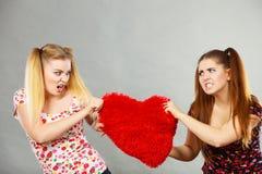 Deux femmes agressives ayant discutent le combat tenant le coeur Images stock