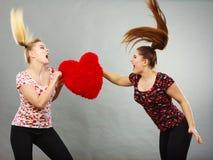 Deux femmes agressives ayant discutent le combat tenant le coeur Images libres de droits